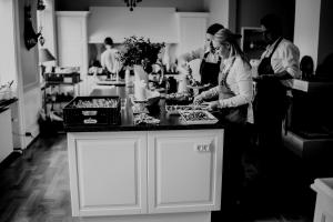 a blond woman and two dark haired men preparing food in a kitchen