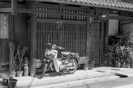 Scooter parked in front of wooden house