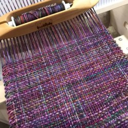 berry colored scarf in progress on rigid heddle loom