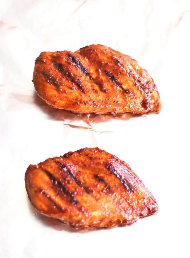 Two pan-grilled and oven baked Bulgogi chicken breasts on a sheet of foil before slicing