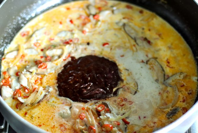 Gochujang marinade and cream and milk cooking with garlic, red chilies, spring onion whites, ginger, and brown Asian mushroom slices in pan.