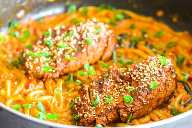 Creamy Spicy Korean Udon Noodles with Bulgogi Chicken in a pan with spring onion green garnish - front view.