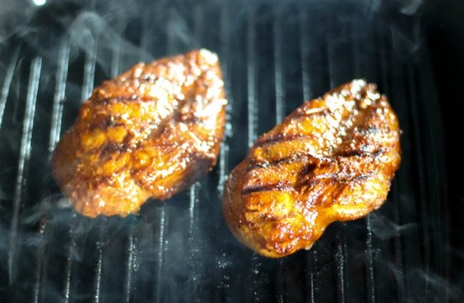 Grilling two bulgogi chicken breasts on a gas grill pan with smoke coming off of the chicken breasts