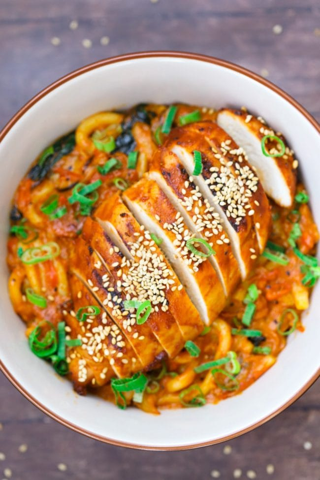 Sliced bulgogi chicken on top of Creamy Dreamy Udon Noodles in bowl on wooden table background with scattered toasted sesame seeds and garnished with spring onion greens.
