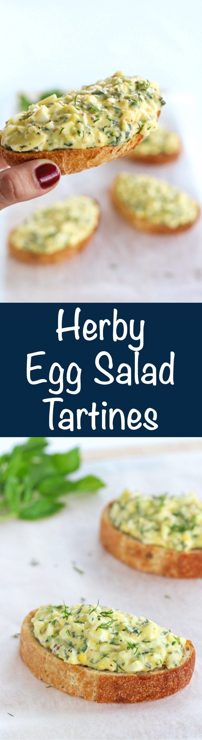 Herby Egg Salad Tartines on a white nonstick cooking paper background with mint leaves with stem in the back. Hand is holding up an egg salad tartine as if ready to take a bite.