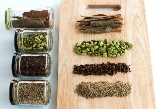 Garam masala ingredients on a chopping board - cassia bark, cardamom pods, whole cloves, cumin seeds. Next to the wooden chopping board are glass airtight jars laid down with each of the ingredients.