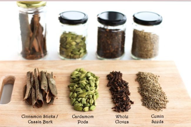 Garam masala ingredients on a chopping board - cassia bark, cardamom pods, whole cloves, cumin seeds. Behind the wooden chopping board are glass airtight jars with each of the ingredients.