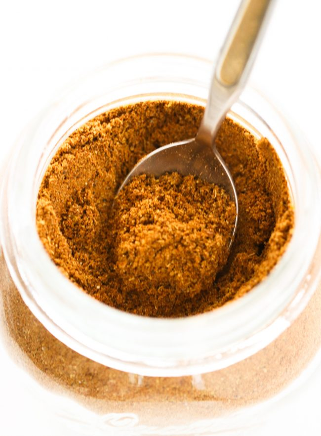 Garam Masala in a glass mason jar with a teaspoon sticking out of it from the right side.
