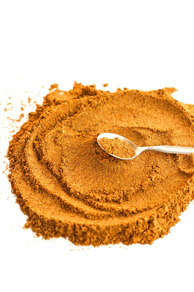 Garam masala spread out in a circular motion on a white background with a teaspoon that has a bit of the garam masala on it.
