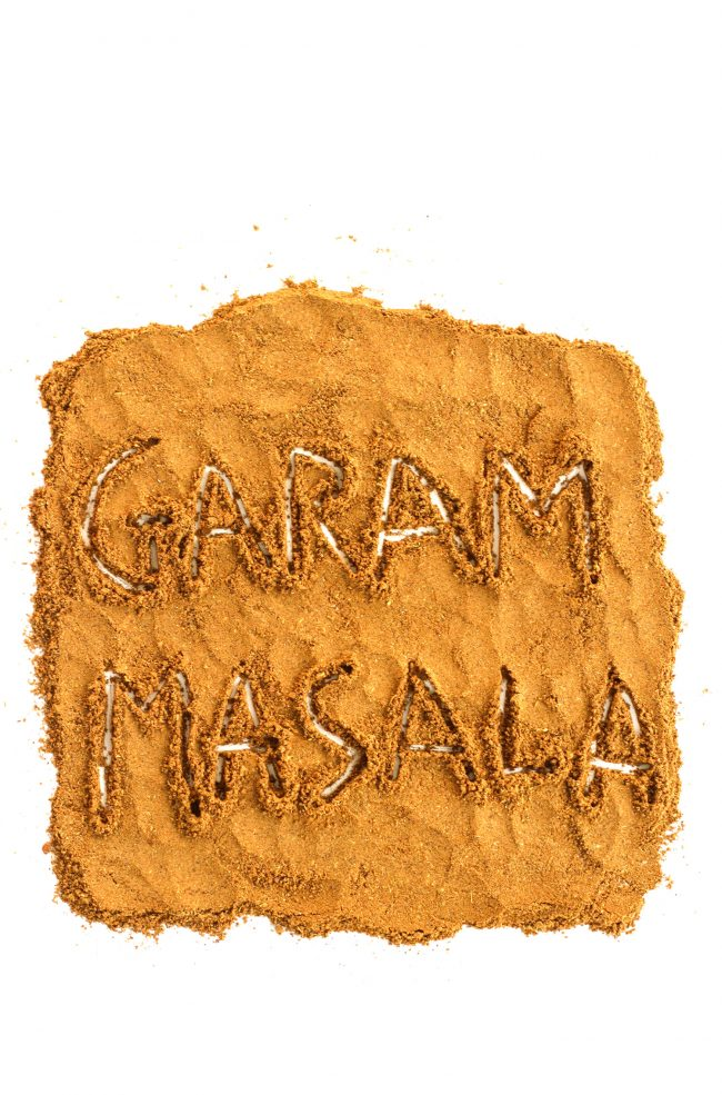 """Garam masala spread in a large square on a white background with the the letters """"G-A-R-A-M M-A-S-A-L-A"""" engraved on the actual garam masala spice."""