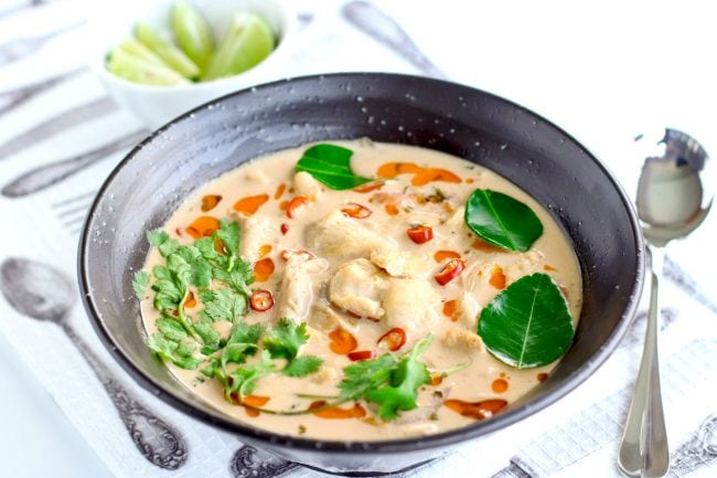 Tom Kha Gai in a black bowl, garnished with coriander leaves, kaffir lime leaves, freshly chopped red chilies, and a splash chili oil. Silver spoon to the side of the bowl and a small bowl with lime wedges behind the soup bowl.