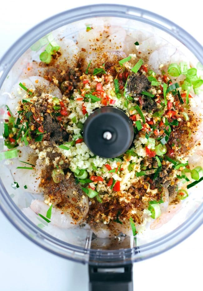 Food processor bowl with ingredients for the Spicy Thai Shrimp Cakes - shrimp meat, Panko bread crumbs, minced garlic, minced Thai red and green chilies, sliced kaffir lime leaves, chopped green snake bean, Thai fish sauce, low sodium soy sauce, ground Thai Red chili pepper, white sugar, kosher salt, and fine ground black pepper.