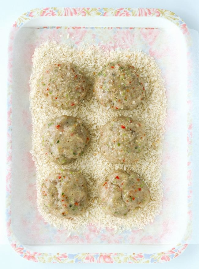 Six uncooked Thai shrimp cake patties on top of pink and white floral tray that is lined with nonstick cooking paper that has bread crumbs on top of it.