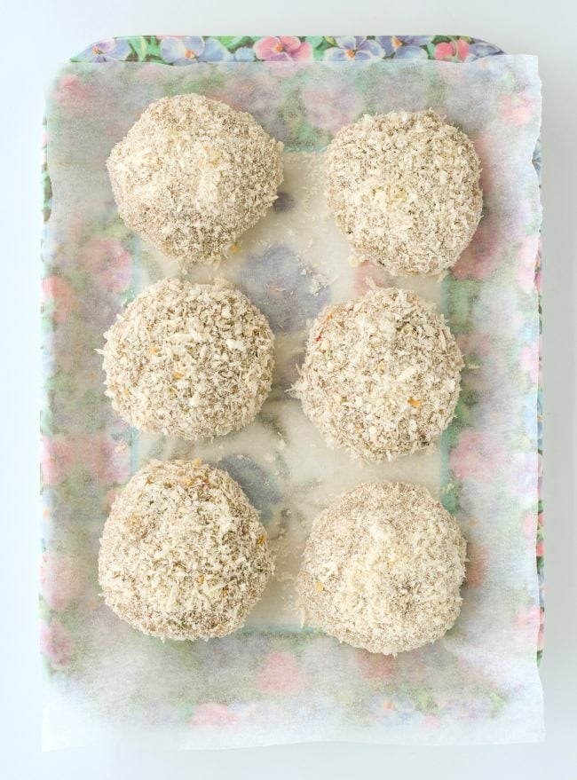Six uncooked Thai shrimp cakes fully coated with bread crumbs on top of nonstick cooking paper on a purple floral tray.