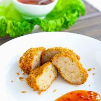 Two spicy Thai shrimp cakes on a white plate cut in half with some Thai sweet chili sauce on the side on the plate.