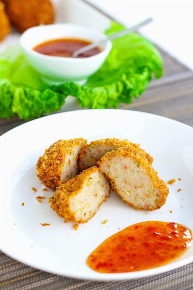 Two spicy Thai shrimp cakes on a white plate cut in half. In the back and diagonally placed to the left is a serving plate with the shrimp cakes, some fresh green lettuce leaves, as well a small serving bowl with Thai sweet chili sauce with a small spoon sticking out of it.