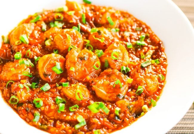 Chili Garlic Shrimp garnished with freshly chopped spring onion greens in a deep white plate.
