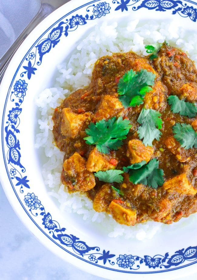 White deep plate with blue patterned rim with Indian Onion Chicken Curry over rice and garnished with coriander leaves cut off from right side of picture. Silver spoon to the side of the plate.