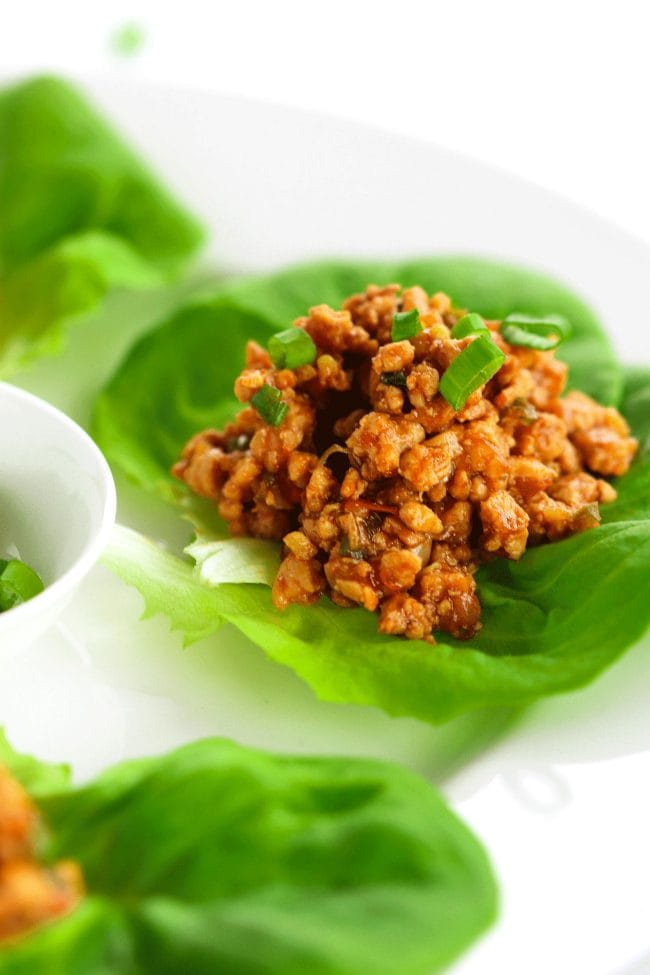 Close up photo of a Chili Chicken Lettuce Cups garnished with spring onion greens on a white round place. In the center of the plate is a small white plate of spring onion greens in the center for garnishing.