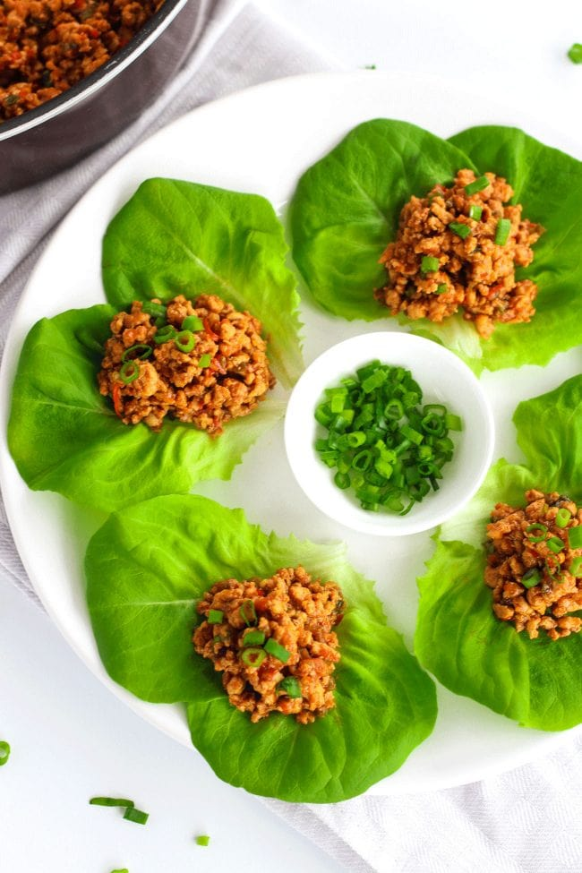 Four Chili Chicken Lettuce Cups on a round white plate with a small plate of spring onion greens in the center for garnishing. Pan of Chili Chicken mince on the top left corner, and scattered spring onion greens on the white background.