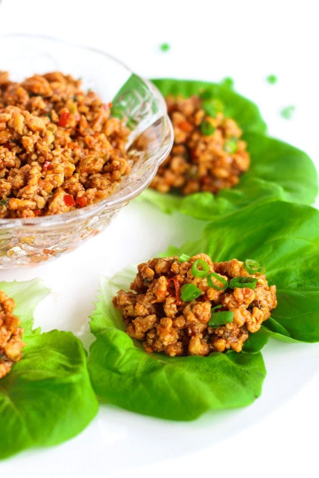 Close up photo of a Chili Chicken Lettuce Cup garnished with spring onion greens on a white round place. In the center of plate is a glass serving bowl filled with chili chicken mince.