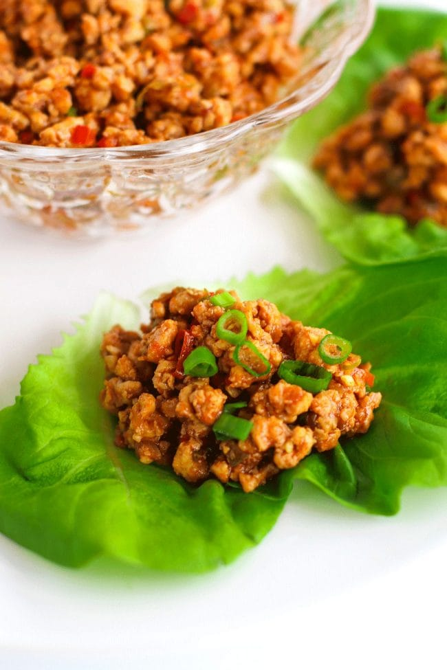 Chili Chicken Lettuce Cups garnished with spring onion greens on a white round place. In the top left of photo (center of plate) is a glass serving bowl filled with chili chicken mince.
