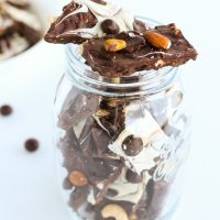 Dark and white chocolate bark pieces with mixed dried fruits and nuts and McVities Dark Chocolate Nibbles stacked in a mason jar on top of a white background. White bowl full of more chocolate bark pieces to left back side of photo.