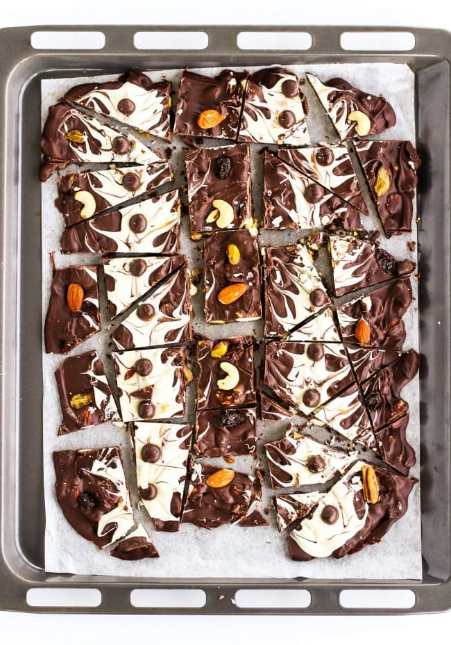 Dark and white chocolate bark (pieces) with mixed dried fruits and nuts and McVities Dark Chocolate Nibbles on top of a nonstick cooking paper layered on a large baking tray.