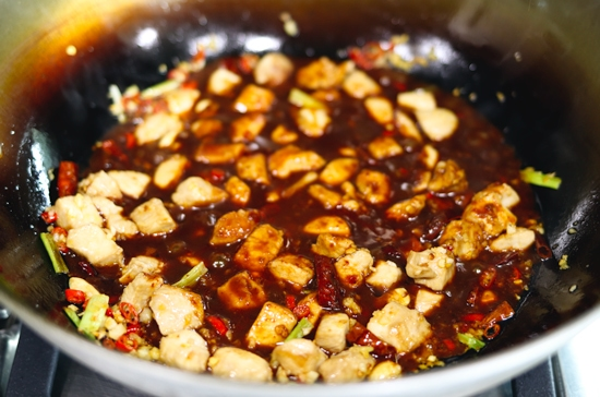 Peanuts, peppercorns, chopped red chilies, minced garlic, minced ginger, spring onion whites, diced chicken pieces and dried red chilies tossed together and simmering in spicy kung pao sauce in a wok