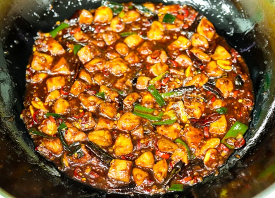 Peanuts, peppercorns, chopped red chilies, minced garlic, minced ginger, spring onion whites, diced chicken pieces and dried red chilies tossed together and simmering in spicy kung pao sauce and spring onion greens tossed together in a wok