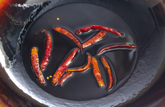 Thai Dried Red Chilies toasting in peanut oil in a wok