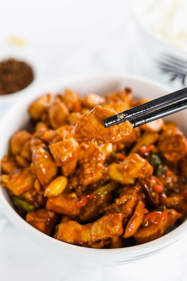 Kung Pao Chicken in a bowl over steamed white rice. Black plastic chopsticks are holding up a piece of chicken over the bowl. Another bowl of steamed white rice and a small dish of Sichuan peppercorns to the side.
