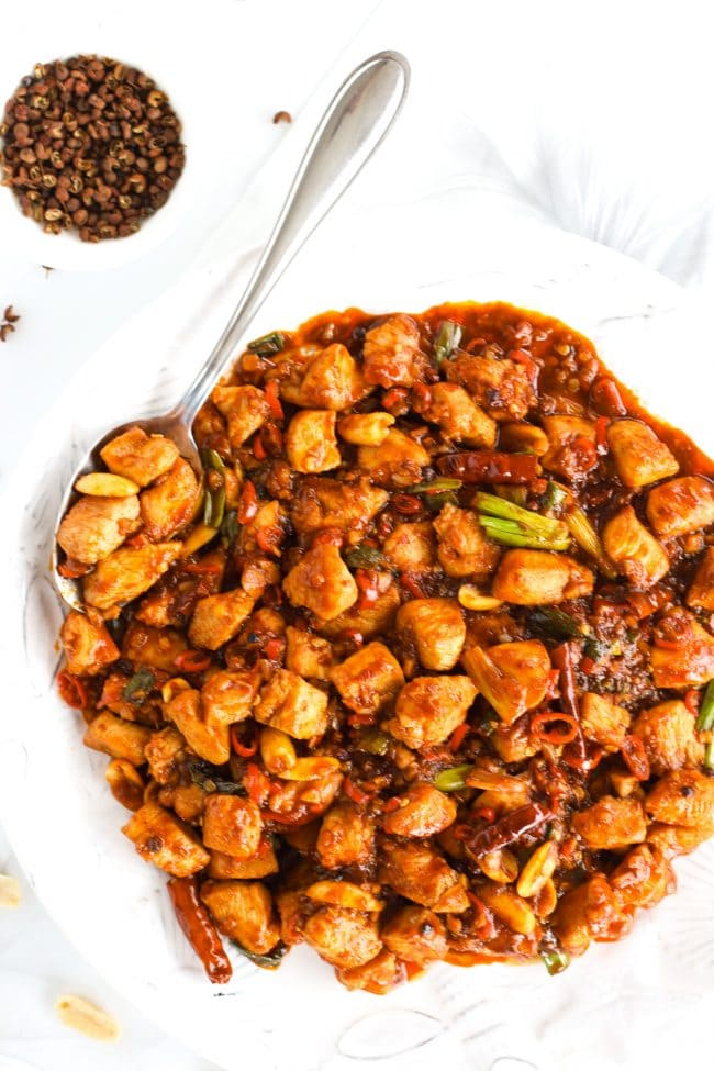 Kung Pao Chicken on a white plate over a black and white flower patterned napkin. Chicken pieces are on top of a spoon in the plate. Peppercorns in a small dish to the side, and peanuts scattered to the side.