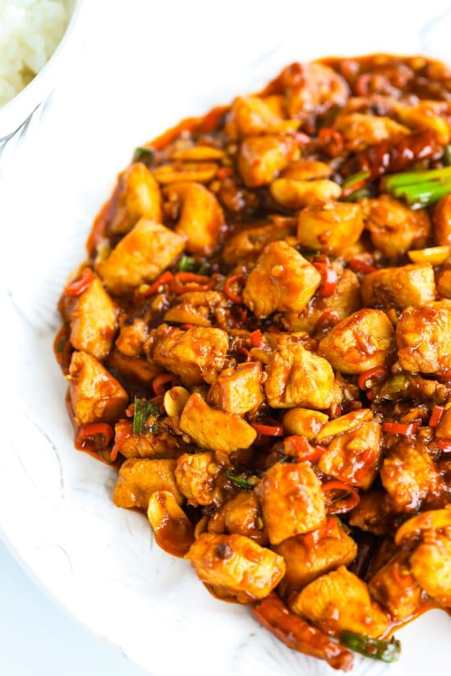 Kung Pao Chicken on a white plate with part of a bowl of steamed white rice to the side.