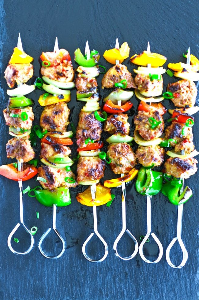 Perfectly grilled marinated chicken pieces, diced bell pepper, and diced onion threaded on metal skewers on top of a black stone plate background. Garnished with chopped spring onion greens.