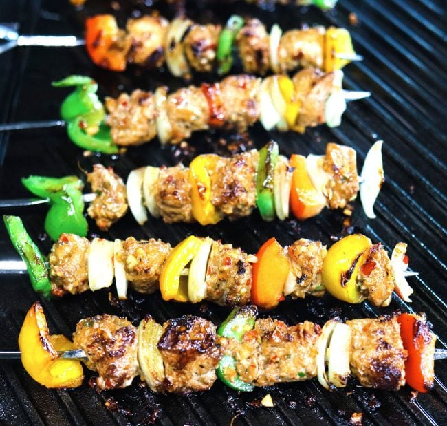 Marinated chicken pieces, diced bell pepper, and diced onion threaded on metal skewers grilling on top of Lodge's cast iron griddle on the stovetop.