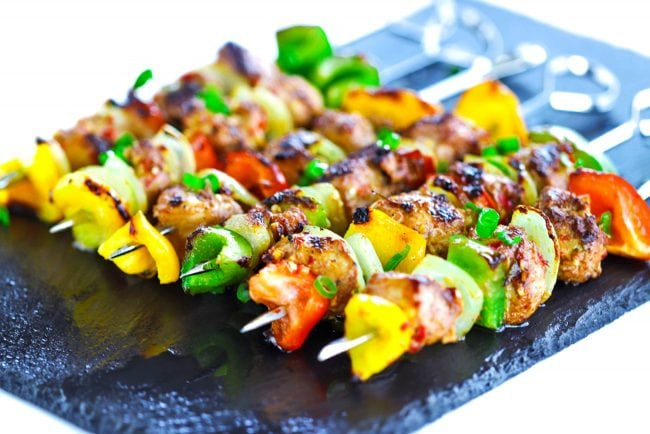 Perfectly grilled Spicy Asian-Cajun Chicken Skewers diagonally placed on top of a black stone plate background. Garnished with chopped spring onion greens.