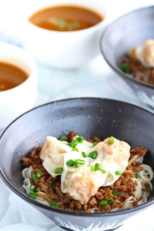Two diagonally placed black bowls of Spicy Dan Dan Noodles with Wontons but without the soup, garnished with spring onion greens, and on top of a grey and white flower patterned napkin. Two small white soup bowls filled with Dan Dan soup to the side of the black bowls.
