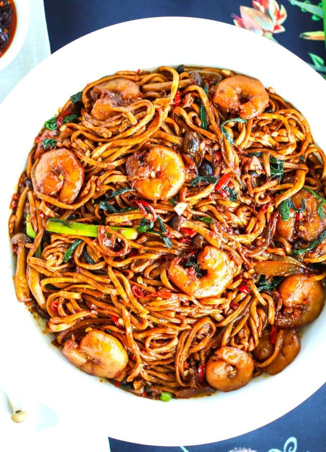 Round white serving bowl filled with Stir-fried E-fu Noodles with Shrimp on top of a navy blue floral design napkin. Serving bowl slightly cut off from right side of photo.