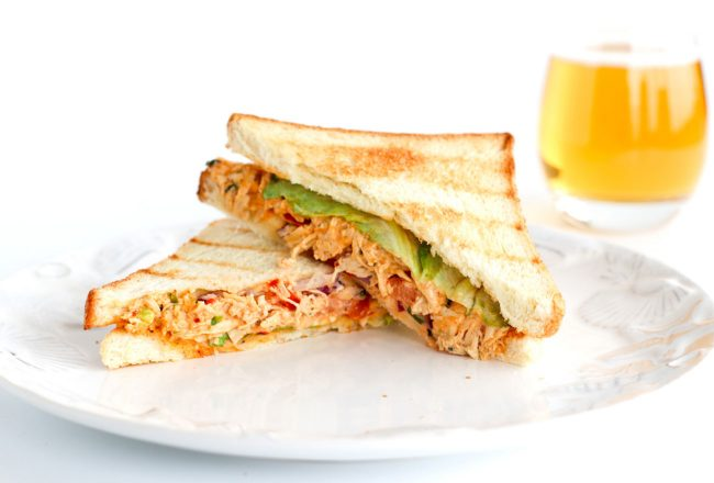 Front view of diagonally sliced Sweet & Spicy Thai Chicken Salad Sandwich stacked at a slanted angle on top of white plate. Glass of apple juice behind the plate.
