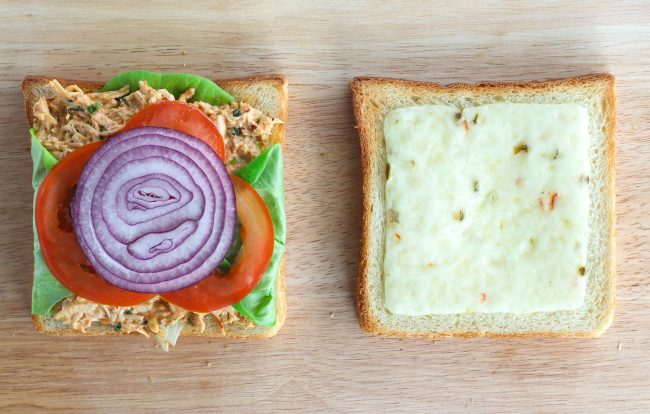 Toasted white bread slices on wooden chopping board - one with  lettuce, Sweet & Spicy Thai Chicken Salad, tomato slices, and red onion on top. The other with pepper jack cheese on top.