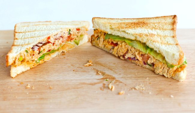 Front view of diagonally sliced Sweet & Spicy Thai Chicken Salad Sandwich on top of wooden board.