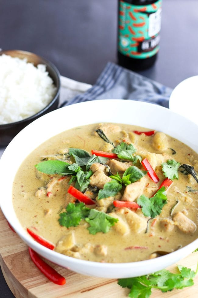 Thai Green Chicken Curry in a large deep white serving bowl on top of a round wooden chopping board which is on top of a blue striped kitchen towel. The curry is garnished with coriander, basil leaves, and red chili strips. Bowl of steamed white rice and white soup ladle to the side. Bottle of ice cold beer in the back on top of a chalkboard backdrop.