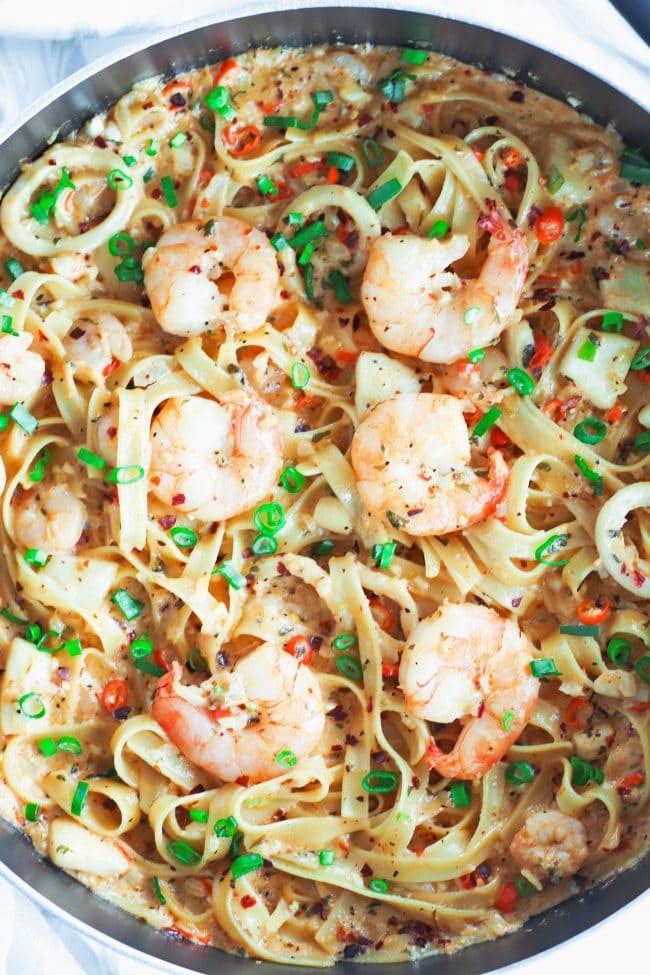 Black pan with Garlic Cream Sauce Seafood Fettuccine cut off from left side of photo. Jumbo juicy shrimp are on top of a bed of pasta in the pan. Garnished with spring onion greens and crushed red pepper flakes.