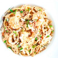 Overhead view of a deep white pasta plate with Garlic Cream Sauce Seafood Fettuccine and a silver fork sticking out of the plate on the side.