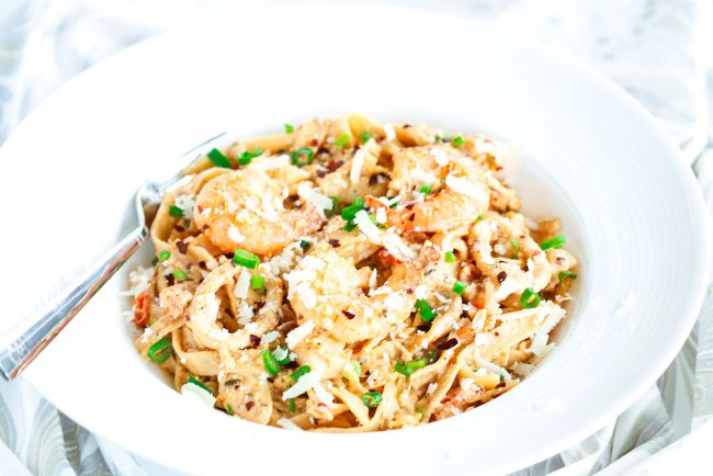 Front view of a deep white pasta plate with Garlic Cream Sauce Seafood Fettuccine and a silver fork sticking out of the plate on the side.