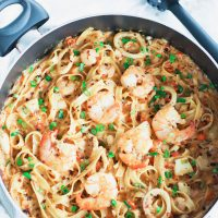 Black pan with Garlic Cream Sauce Seafood Fettuccine cut off from left side of photo. Jumbo juicy shrimp are on top of a bed of pasta in the pan. Garnished with spring onion greens and crushed red pepper flakes. Black pasta server to the side of pan.