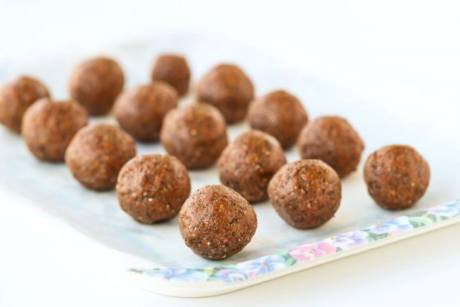 Nutella & Peanut Butter Energy Balls lined up on top of non-stick cooking paper on top of a tray.