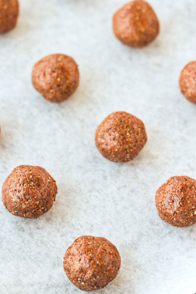 Close up of Nutella & Peanut Butter Energy Balls lined up on top of non-stick cooking paper.