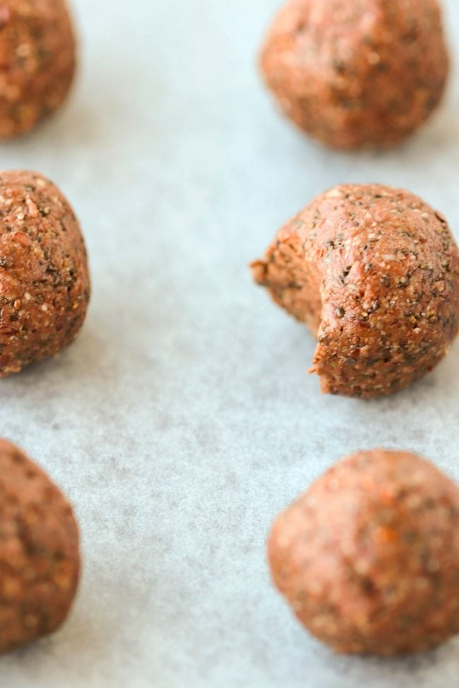 Six Nutella & Peanut Butter Energy Balls lined up on top of non-stick cooking paper. Close up and focus on one energy ball that has a bite taken out of it.